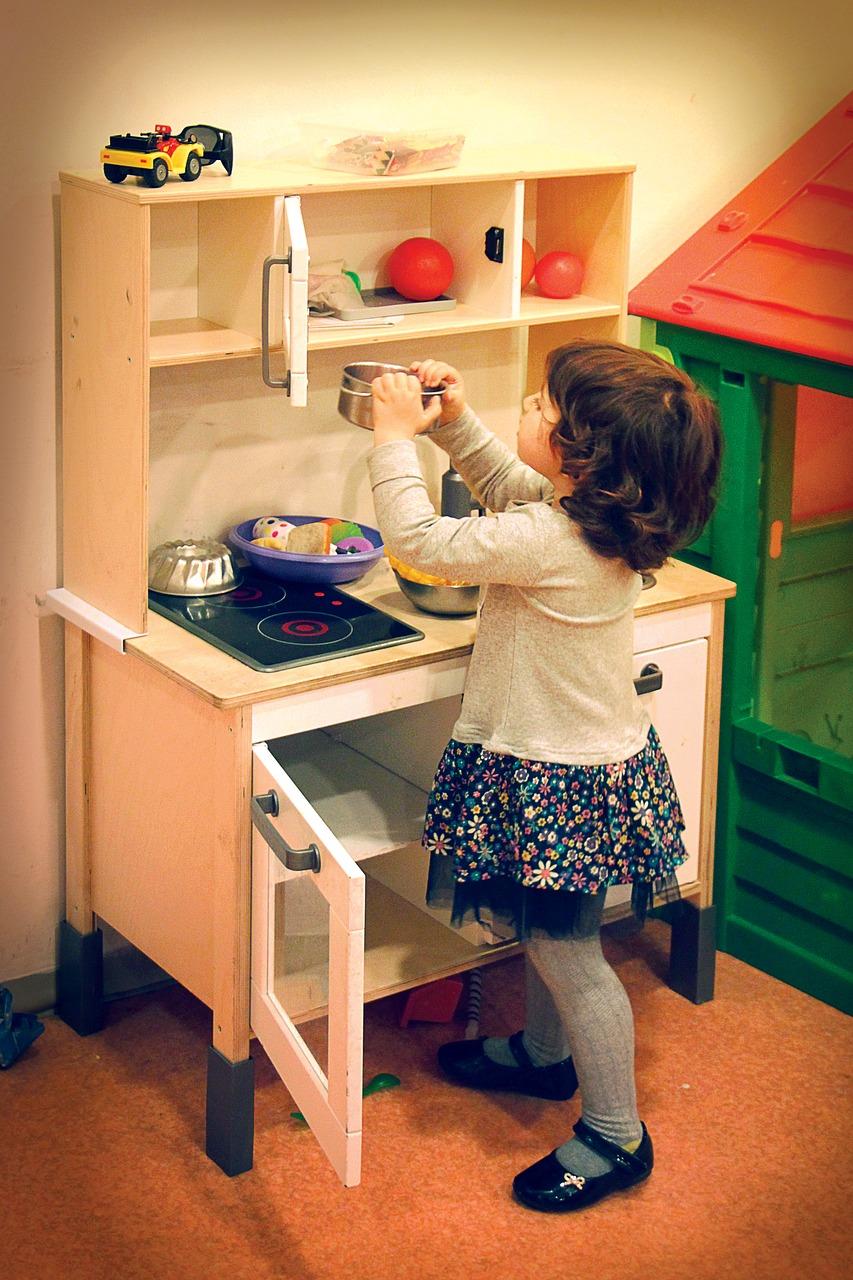Cette petite fille joue avec sa cuisine jouet en bois.